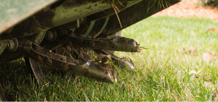a close up of a core aerator pulling plugs out of the soil