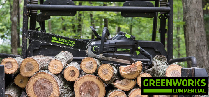 greenworks commercial chainsaw sitting on a pile of logs
